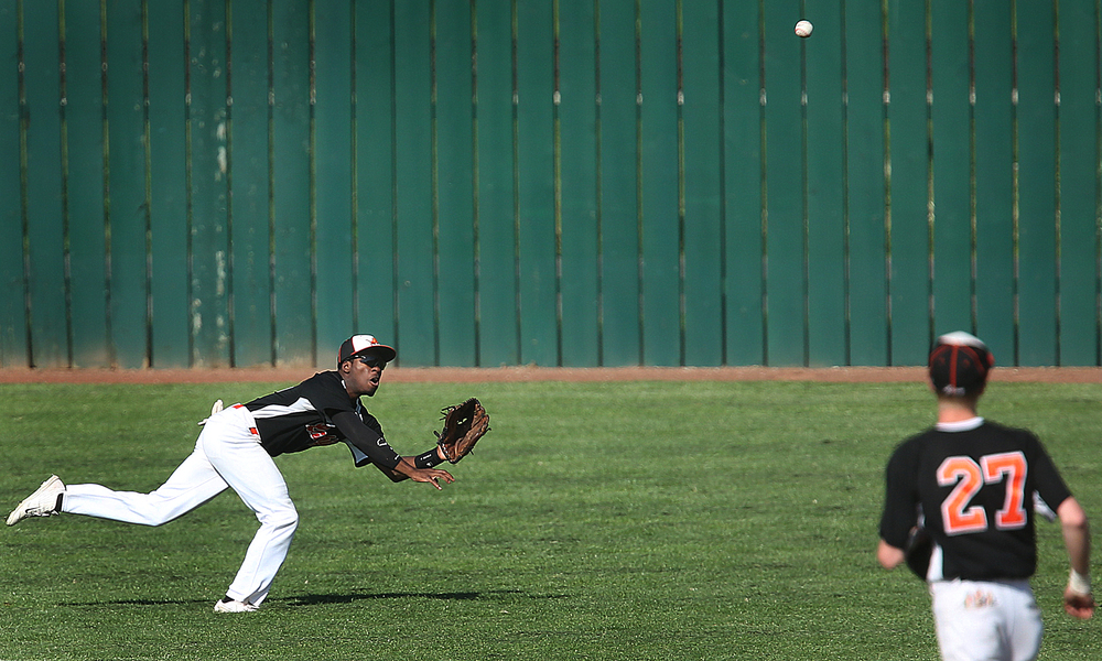 Lanphier left fielder Jared Roulds-Griffin prepares to make a dive for an out hit by SHG player Clayton Taylor in second inning action. The Sacred Heart Griffin Cyclones defeated the Lanphier High School Lions 15-5 to win the championship of the City Series Baseball Tournament at Robin Roberts Stadium in Springfield on Tuesday, May 12, 2015. David Spencer/The State Journal-Register