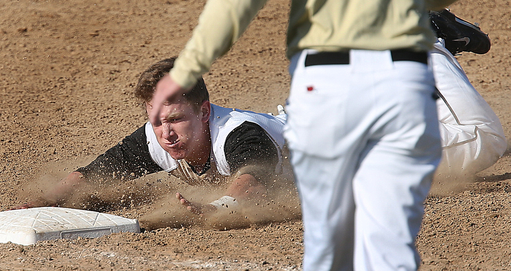 SHG baserunner Justin Zanger gets a face full of dirt as he slides safely into third base during third inning action. The Sacred Heart Griffin Cyclones defeated the Lanphier High School Lions 15-5 to win the championship of the City Series Baseball Tournament at Robin Roberts Stadium in Springfield on Tuesday, May 12, 2015. David Spencer/The State Journal-Register