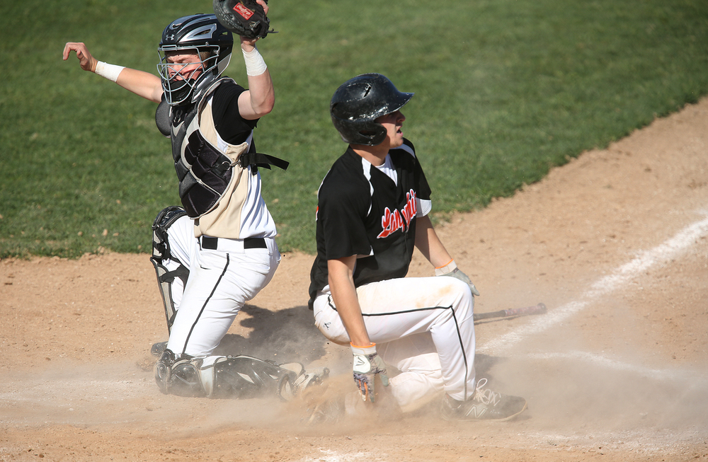 In third inning action, Lanphier baserunner Kody Childers evades the tag by SHG catcher Mason Hale to score. The Sacred Heart Griffin Cyclones defeated the Lanphier High School Lions 15-5 to win the championship of the City Series Baseball Tournament at Robin Roberts Stadium in Springfield on Tuesday, May 12, 2015. David Spencer/The State Journal-Register
