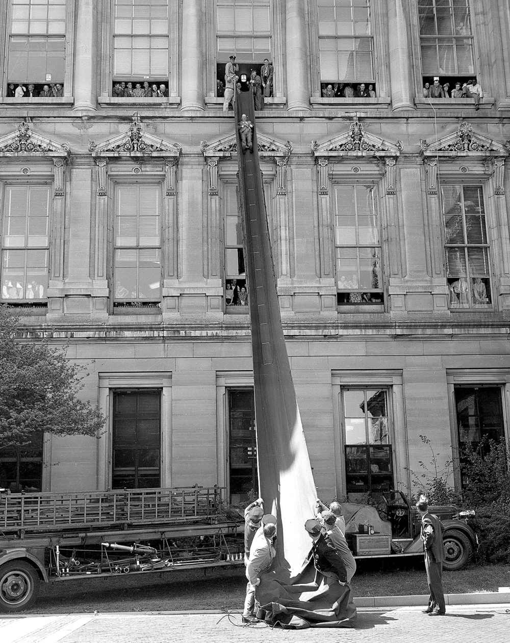 "Springfield firefighters test a collapsible fire chute May 17, 1949 at the Illinois State Capitol. Members of the Springfield Fire Department hold the bottom of the ""Eastman evacuator,"" a collapsible fire chute while State Rep. Orville Chapman slides from a third floor window. 