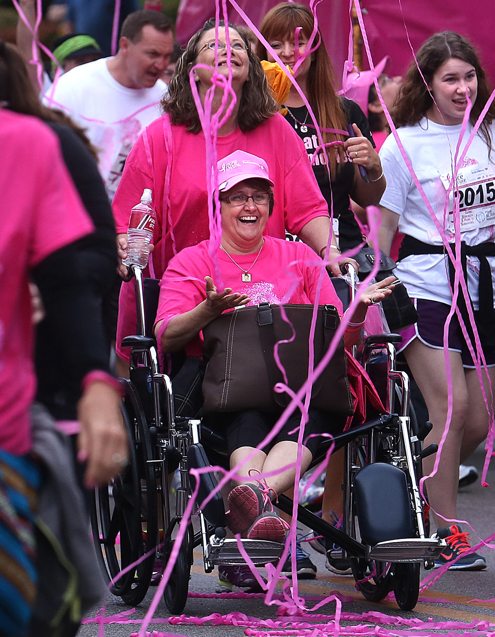 Dinah Boehm of Shelbyville, a nine-month breast cancer survivor, holds out her hands to catch streamers shot into the air at the beginning of the race on Second Street Friday night. Sandy Falk of Effingham was steering her best friend from behind. David Spencer/The State Journal-Register