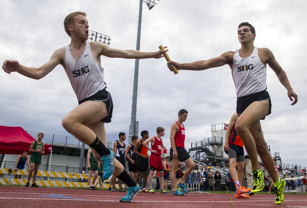 Sacred Heart-Griffin's Sam Rogers takes the baton from Nate Fierstos, right, to run the final leg of the Boys 4x800m Relay during the Boys Central State Eight Track & Field Meet at Glenwood High School, Friday, May 15, 2015, in Chatham, Ill. SHG won the race with a time of 8:07.30. Justin L. Fowler/The State Journal-Register