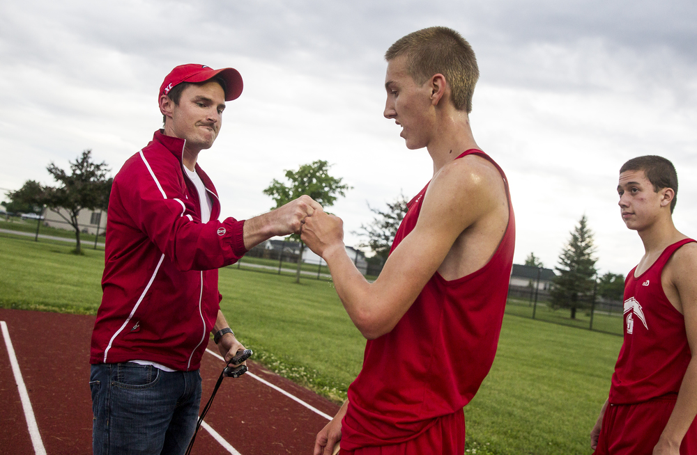 Glenwood's Landon Skelly gets a fist bump from coach Mike Garber after winning the Boys 3200m Run with a time of 9:46.75 during the Boys Central State Eight Track & Field Meet at Glenwood High School, Friday, May 15, 2015, in Chatham, Ill. Justin L. Fowler/The State Journal-Register