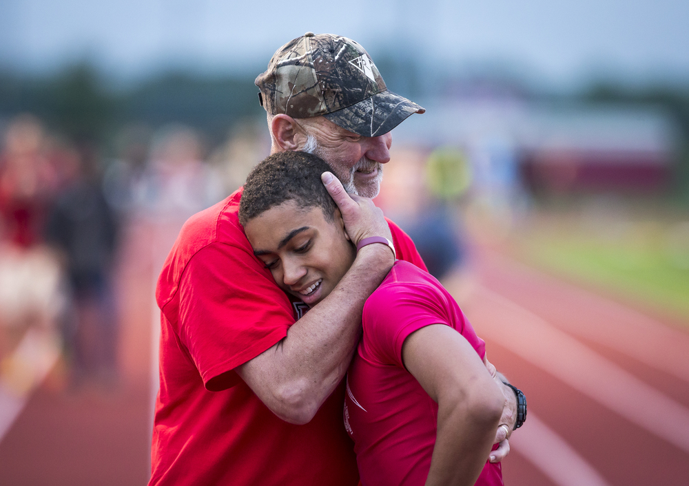 Glenwood boys track coach Len Onken hugs Kameron Corner after he helped the Titans finish second in the Boys 4x200m Relay during the Boys Central State Eight Track & Field Meet at Glenwood High School, Friday, May 15, 2015, in Chatham, Ill. Corner suffered an asthma attack the night before and was able to recover and compete in six different events including preliminaries. Justin L. Fowler/The State Journal-Register