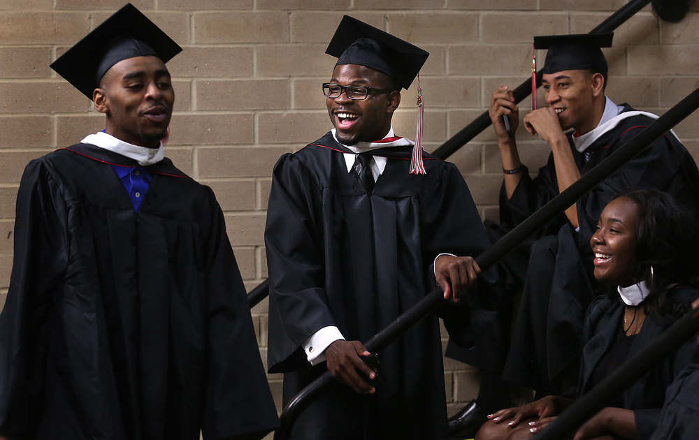 Benedictine graduate Demetrius Bonner, center, who earned his Bachelor of Arts in Criminal Justice degree Saturday, laughs before the Commencement with friends and fellow graduates, including Travon Porter at left of Champaign. David Spencer/The State Journal-Register