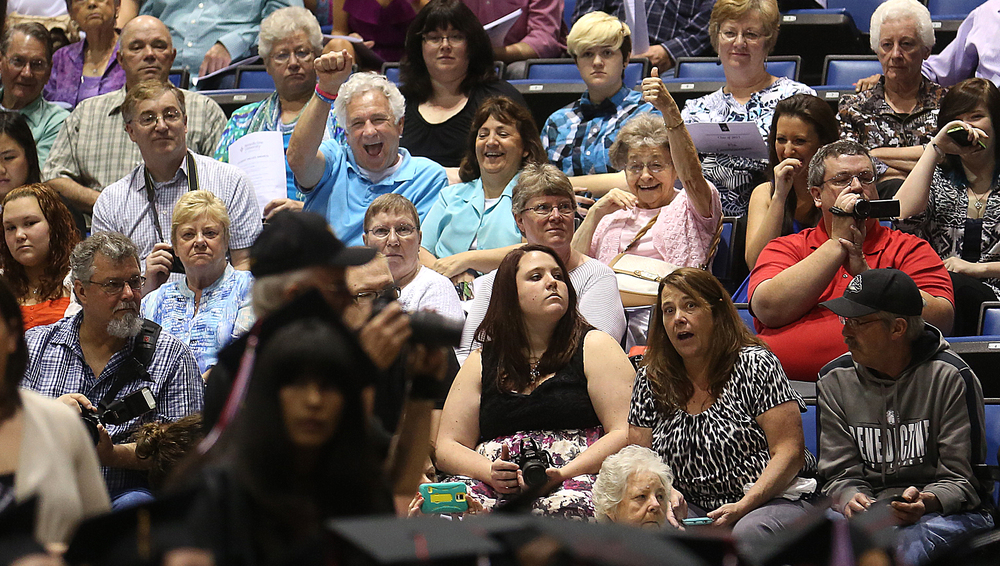 A thumbs up by one member of the audience is directed at a graduate processing on the floor of the convention center Saturday morning. David Spencer/The State Journal-Register