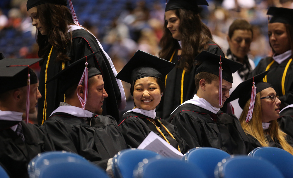 Graduate Brittany Limper smiles at center shortly after taking her seat along with others Saturday morning. Limper, who earned a Bachelor Arts in Communication Arts was the school's Procopian Award recipient and spoke during the ceremony.David Spencer/The State Journal-Register