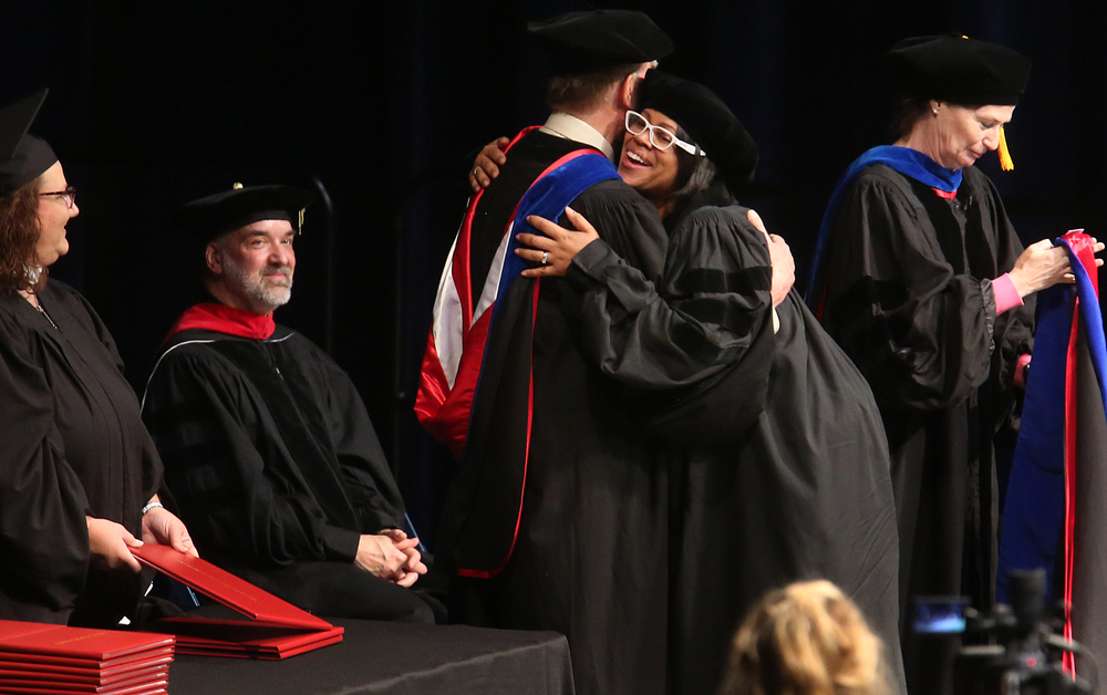 Tiffany Slater, who received her Doctor of Philosophy, Organization Development degree, hugs David Coghlan, her Dissertation Chair before being hooded by him. Slater was one of three students receiving their doctorates, along with Aaron Slater, Jr. and Regina Troxell. David Spencer/The State Journal-Register