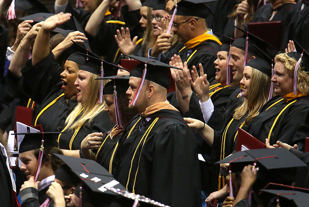 New graduates celebrate after moving their mortar board tassels from right to left after receiving their diplomas. David Spencer/The State Journal-Register