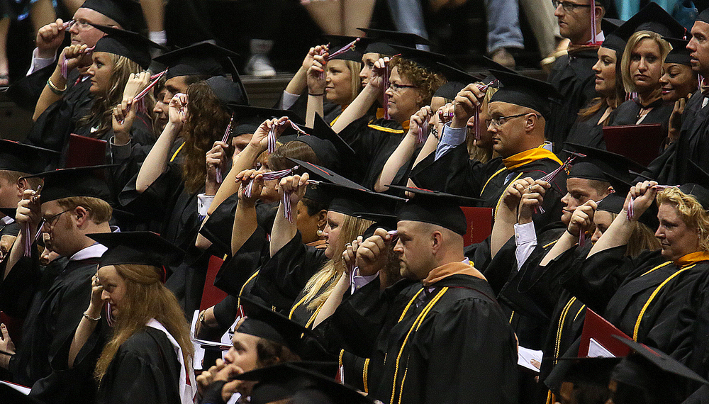 New graduates prepare to move their mortar board tassels from right to left after receiving their diplomas. David Spencer/The State Journal-Register