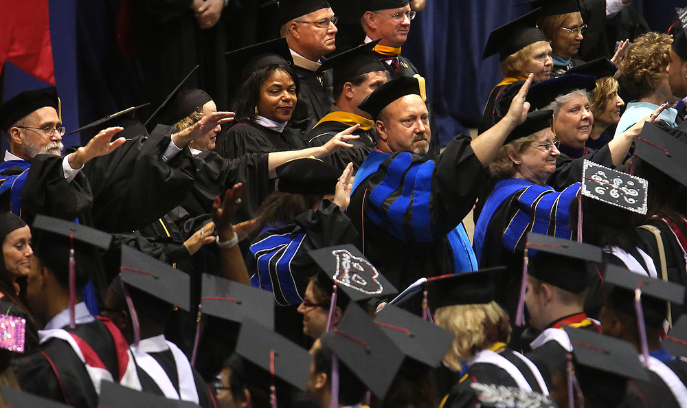 In a show of respect to the new graduates, Benedictine faculty members faced the students with their arms extended in a sign of respect to their achievment. David Spencer/The State Journal-Register