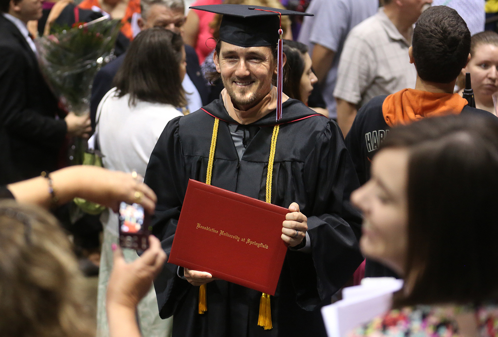 Graduate Adam Gabany, who earned his Bachelor of Business Administration in Management and Organizational Behavior, has his photo taken by a family member at the conclusion of the commencement ceremony Saturday morning. David Spencer/The State Journal-Register