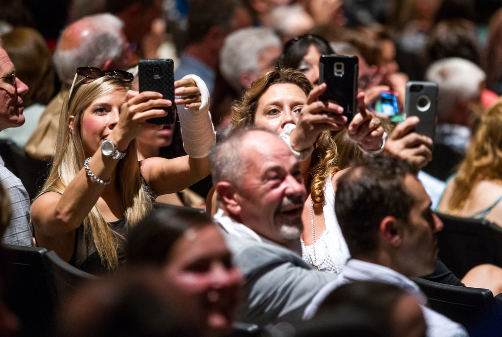 Family and friends use their cell phones to capture the graduates as they head towards the stage for the processional during the 99th Commencement for Pleasant Plains High School at Sangamon Auditorium, Sunday, May 17, 2015, in Springfield, Ill. Justin L. Fowler/The State Journal-Register