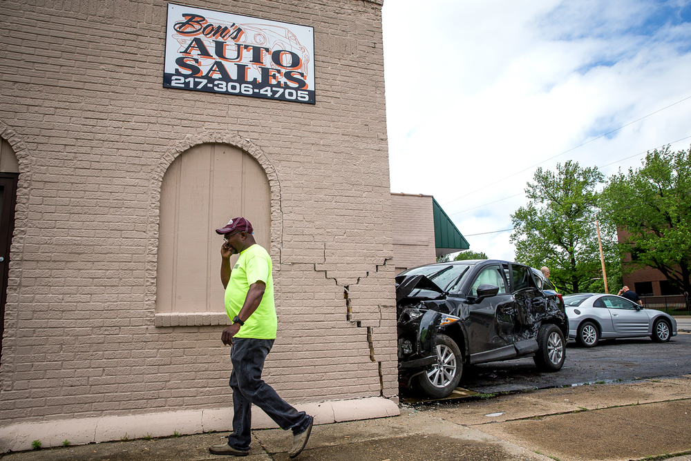A two vehicle accident at the intersection of 11th Street and North Grand Avenue ended with an SUV taking out a traffic light and colliding with the building of Bon's Auto Sales, Monday, May 11, 2015, in Springfield, Ill. Justin L. Fowler/The State Journal-Register