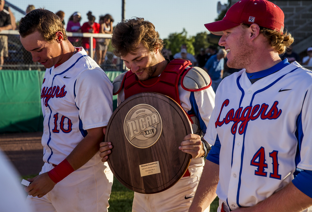 Lincoln Land Community College catcher Carter Pranger (6) carries the trophy for the team after the Loggers defeated John Wood Community College 6-3 in ten innings to win the NJCAA Region 24 Tournament at Claude Kracik Field, Monday, May 18, 2015, in Springfield, Ill. Justin L. Fowler/The State Journal-Register