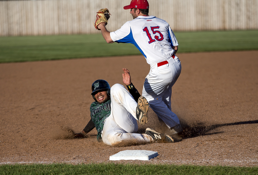 John Wood's Jalen Poindexter (22) slides safely into third base against Lincoln Land Community College third baseman Sam Goode (15) in the 9th inning during the NJCAA Region 24 Tournament at Claude Kracik Field, Monday, May 18, 2015, in Springfield, Ill. Justin L. Fowler/The State Journal-Register