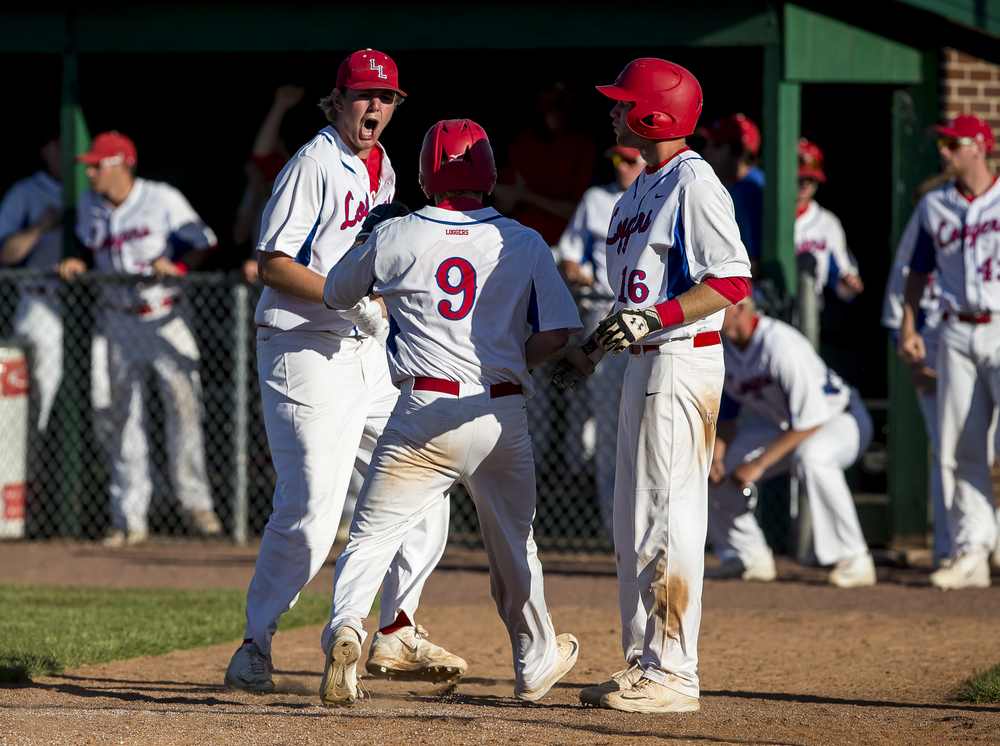 Lincoln Land Community College's Konnor Aherin (21) celebrates as Nick Lonergan (9) crosses home plate to tie the game 3-3 against John Wood Community College in the 8th inning during the NJCAA Region 24 Tournament at Claude Kracik Field, Monday, May 18, 2015, in Springfield, Ill. Justin L. Fowler/The State Journal-Register