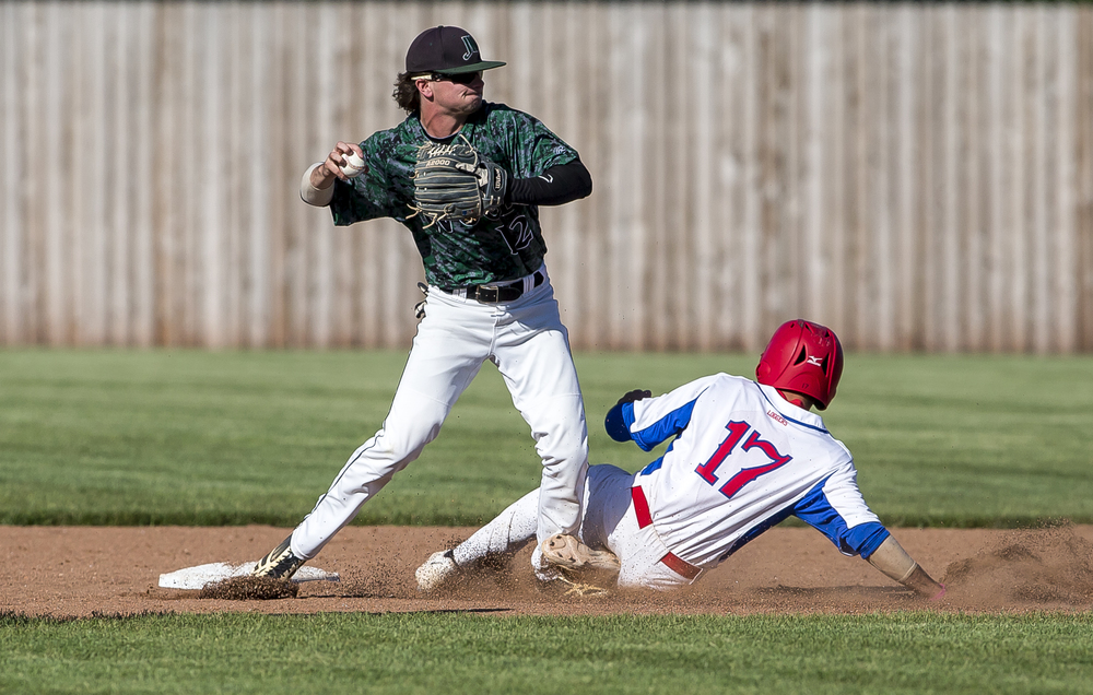 Lincoln Land Community College's Zach Barnhart (17) disrupts a double play as he slides into second against John Wood Community College shortstop Zane Corbell (12) in the 5th inning during the NJCAA Region 24 Tournament at Claude Kracik Field, Monday, May 18, 2015, in Springfield, Ill. Justin L. Fowler/The State Journal-Register