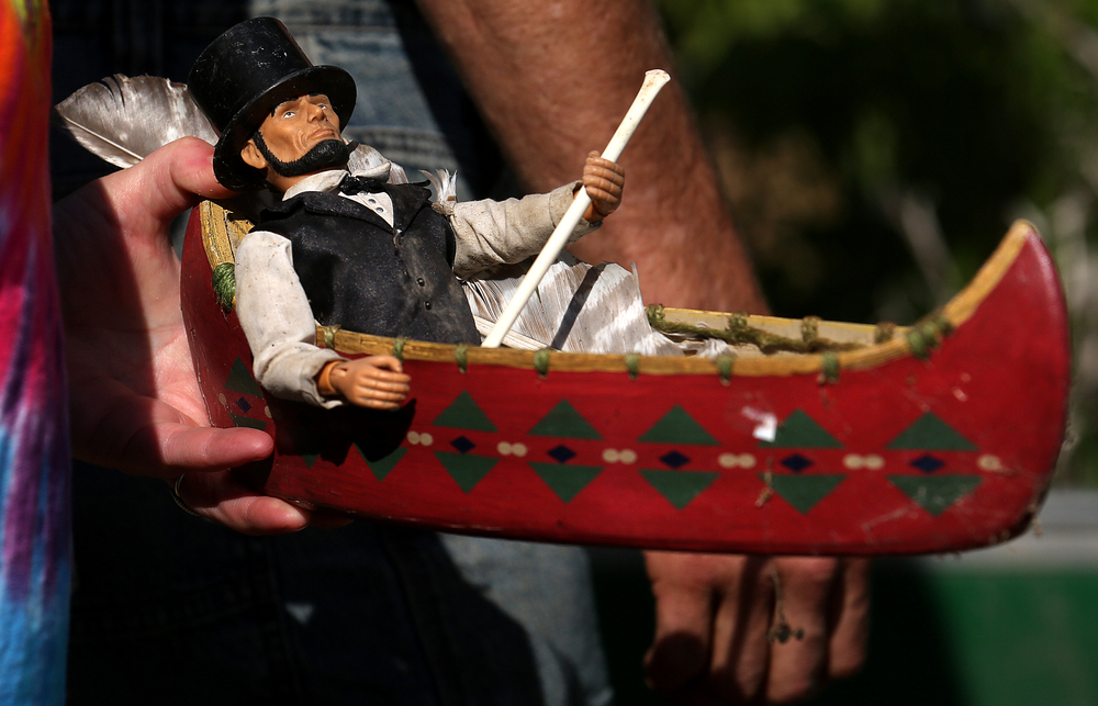 Paddler Randee Harbert of Athens carries a momento found on the Sangamon River three years ago when she first took part in the race: an Abraham Lincoln doll seated with paddle in a miniature canoe. Harbert secured miniature Abe to the bow of her own canoe on Saturday. David Spencer/The State Journal-Register