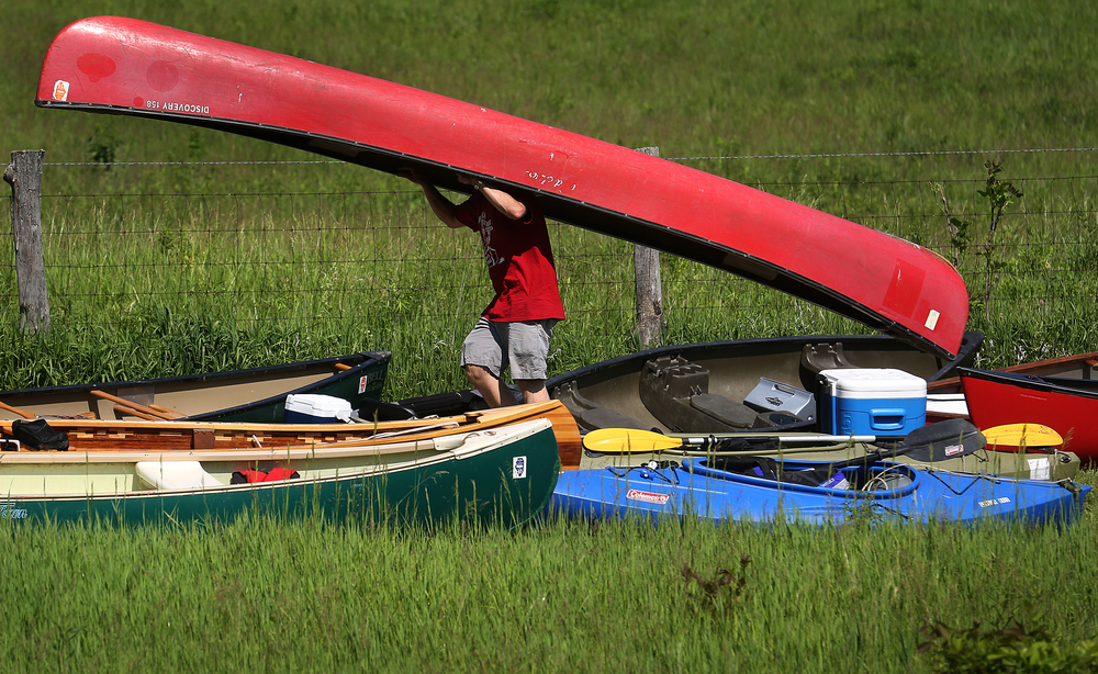 Race director Scott Hewitt portages a canoe to the staging area near the start of the race off of Irwin Bridge Rd. Saturday morning. David Spencer/The State Journal-Register