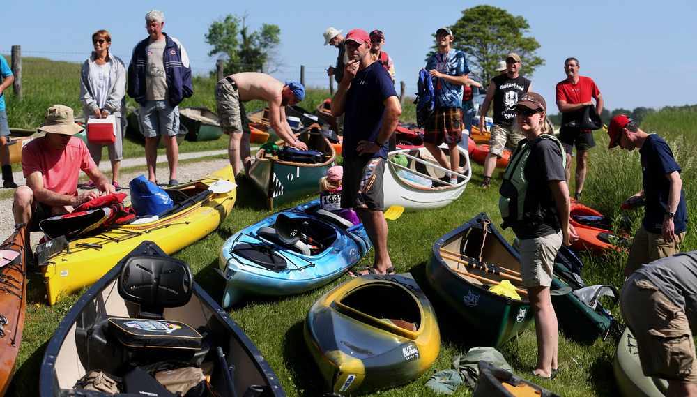 Paddlers prepare to portage their boats to the start area on the river Saturday morning. David Spencer/The State Journal-Register