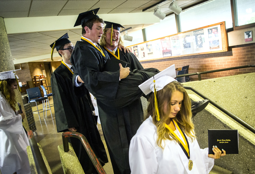 Sacred Heart-Griffin graduate Quinn Oseland, center, jokingly starts to carry Michael Ziegler, down the stairs after the Class of 2015 received their diplomas during their graduation ceremony at Sangamon Auditorium, Sunday, May 24, 2015, in Springfield, Ill. Justin L. Fowler/The State Journal-Register