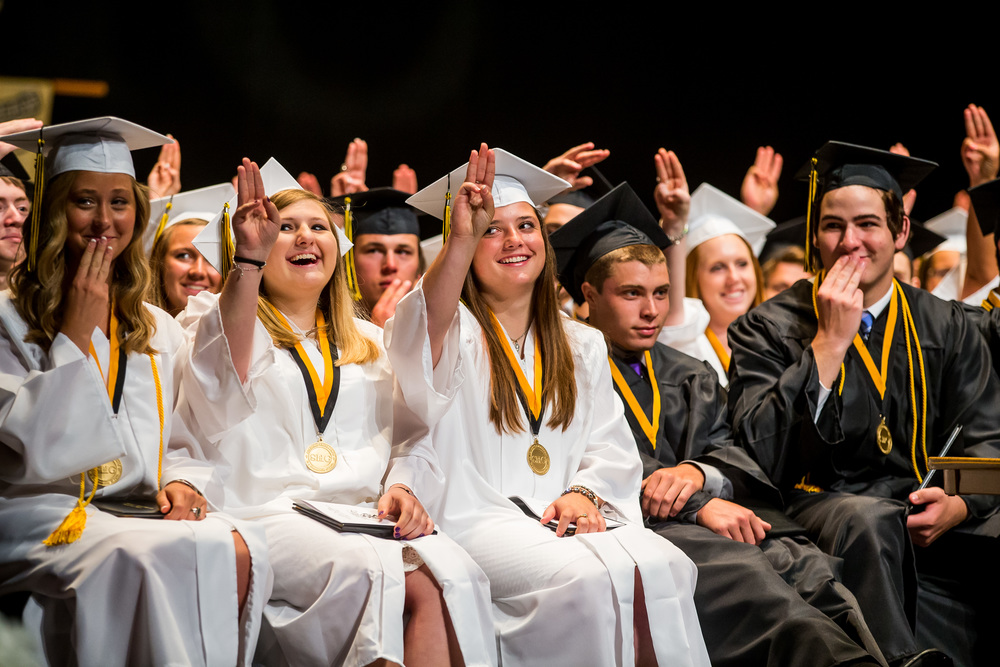 """Sacred Heart-Griffin graduates give the hand signal from the the """"Hunger Games"""" at the conclusion of Valedictorian Cody Prosperini's speech during the graduation ceremony for Sacred Heart-Griffin at Sangamon Auditorium, Sunday, May 24, 2015, in Springfield, Ill. Justin L. Fowler/The State Journal-Register"""