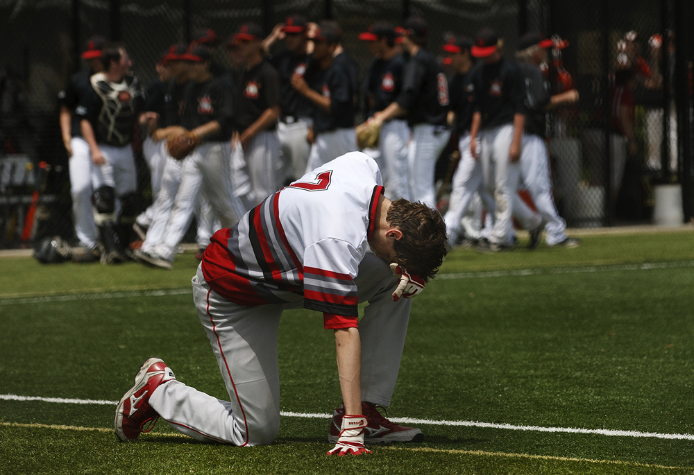 Jacksonville's Drew Haggerty kneels on the first base line after Springfield claimed the last out and a 5-1 win during the 3A SHG Regional Monday, May 25, 2015. Ted Schurter/The State Journal-Register