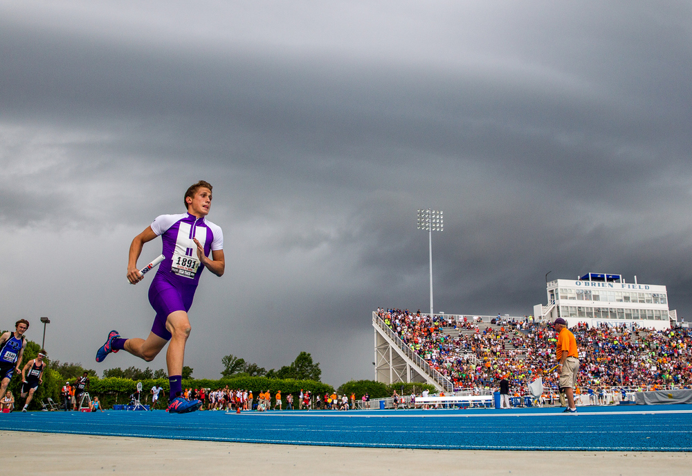 Harrisburg's Michael Victoria rounds the turn as a storm moves in on the first leg of the Class 2A 4x400m Relay during the IHSA Boys Track and Field State Finals at O'Brien Stadium, Saturday, May 30, 2015, in Charleston, Ill. Justin L. Fowler/The State Journal-Register