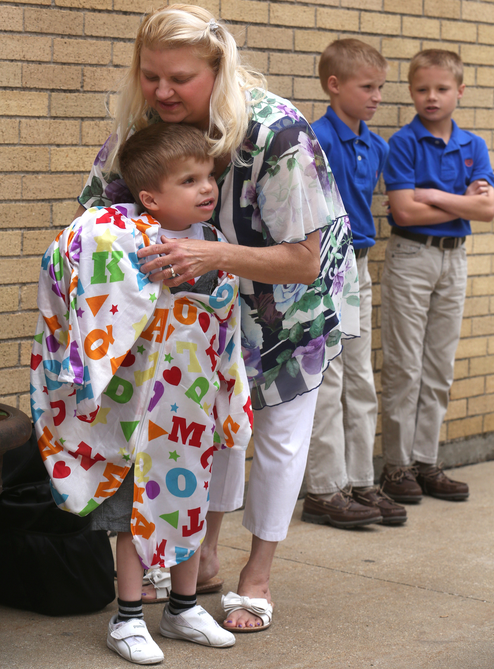 Deanna Planitz puts a graduation gown on her son Jordan outside the school gym Sunday afternoon while Jordan's older brothers Joshua and Jeremy Planitz wait at right. David Spencer/The State Journal-Register