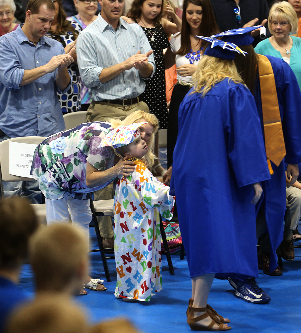 Deanna Planitz gives her son Jordan a kiss moments before he was lead onstage by school valedictorian Bethany Daniels and class president Mackenzie Lyons to receive his diploma. David Spencer/The State Journal-Register