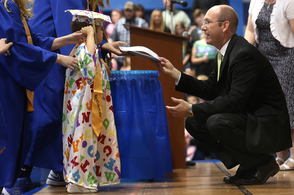 Tri-City principal Dustin Day presented Jordan Planitz a diploma onstage in the school gym Sunday afternoon. David Spencer/The State Journal-Register