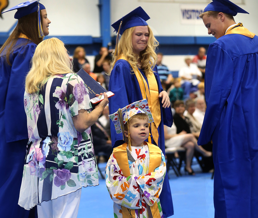Class president Mackenzie Lyons at center shed a few tears-along with many attending Sunday's graduation- after Jordan Planitz received his honorary diploma. David Spencer/The State Journal-Register