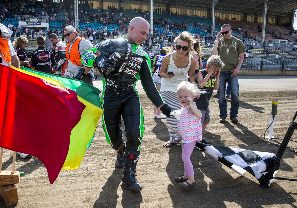 Bryan Smith hands his niece, Ella Murphy, a towel as wind kicks up a dust on the track as he heads to the podium after winning the AMA Pro Flat Track Grand National Championship Springfield Mile at the Illinois State Fairgrounds, Sunday, May 24, 2015, in Springfield, Ill. Justin L. Fowler/The State Journal-Register