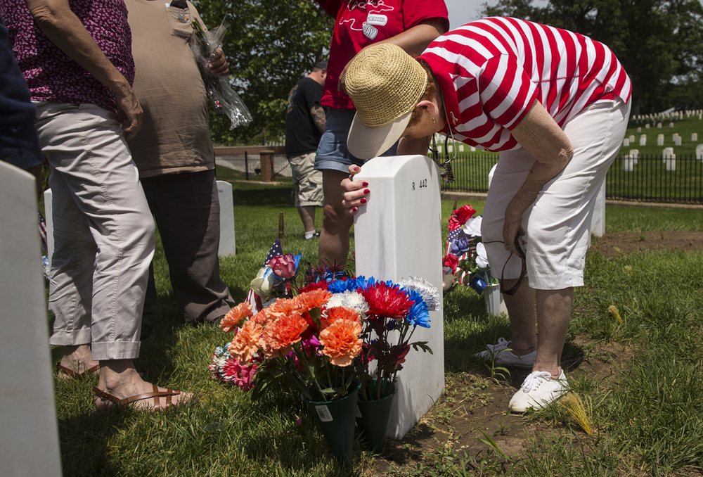 Mary Hartke holds tight to the gravestone of her son James Lee before Memorial Day services at Camp Butler National Cemetery Monday, May 25, 2015. Hartke and family members and friends placed flowers and other mementos on his grave during the first Memorial Day since his death.  Ted Schurter/The State Journal-Register