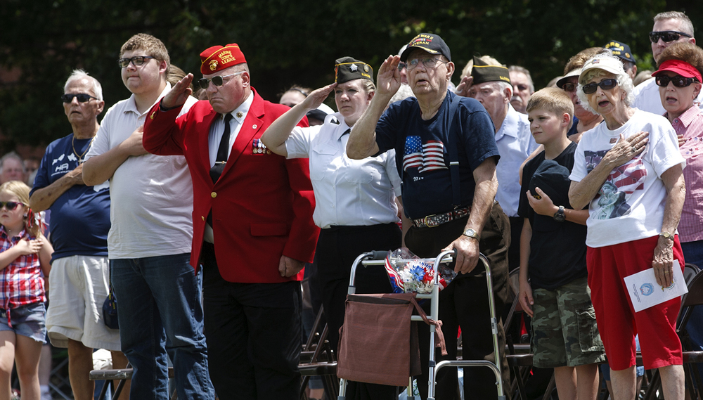 "Members of the crowd salute during the playing of ""Taps"" during Memorial Day services at Camp Butler National Cemetery Monday, May 25, 2015. Ted Schurter/The State Journal-Register"