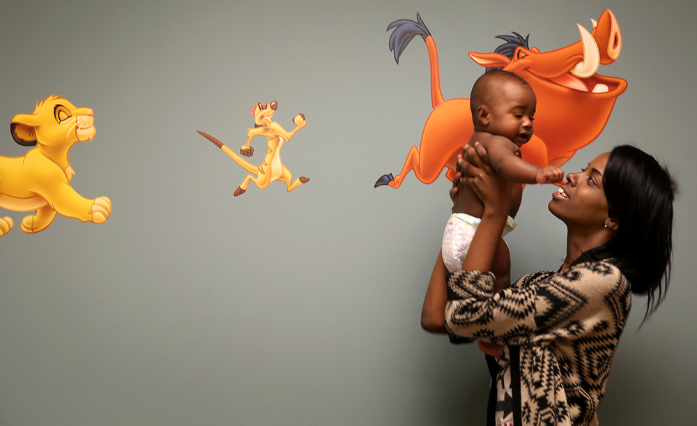 Zakyria Horton entertains her six-month-old son Elijah Moore before he received a checkup at the Central Counties Health Center on Thursday, May 21, 2015. The 11-year-old Central Counties Health Center recently completed a $4.5 million expansion project, including13 examination rooms, an expanded waiting room and in-house Schnucks pharmacy. David 