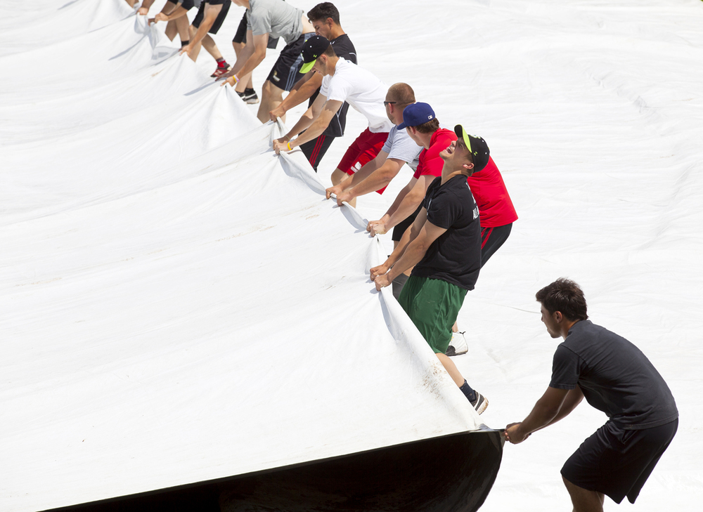The Springfield Sliders baseball team was put to use pulling off the tarp that protects the infield at Robin Roberts Stadium before beginning practice Tuesday, May 26, 2015. Rich Saal/The State Journal-Register