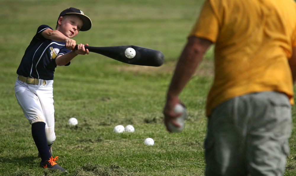 Joey Ruzic, 9, of Springfield, a team member for the Bandits of the Springfield Southwest Baseball Association, finds the sweet spot for a pitch thrown by his father Joe Ruzic at Lincoln Park on Thursday, May 28, 2015. Using an oversized plastic bat and as many as 60 plastic balls during a practice session, Joe Ruzic said he and his son practice often in order to hone batting skills. Joey was dressed up because he was scheduled to play in a game at Rotary Park on Thursday night. David Spencer/The State Journal-Register