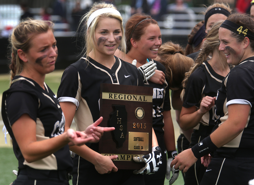 SHG player Makenzie Trees holds the championship trophy while surrounded by teammates at the end of the game. David Spencer/The State Journal-Register