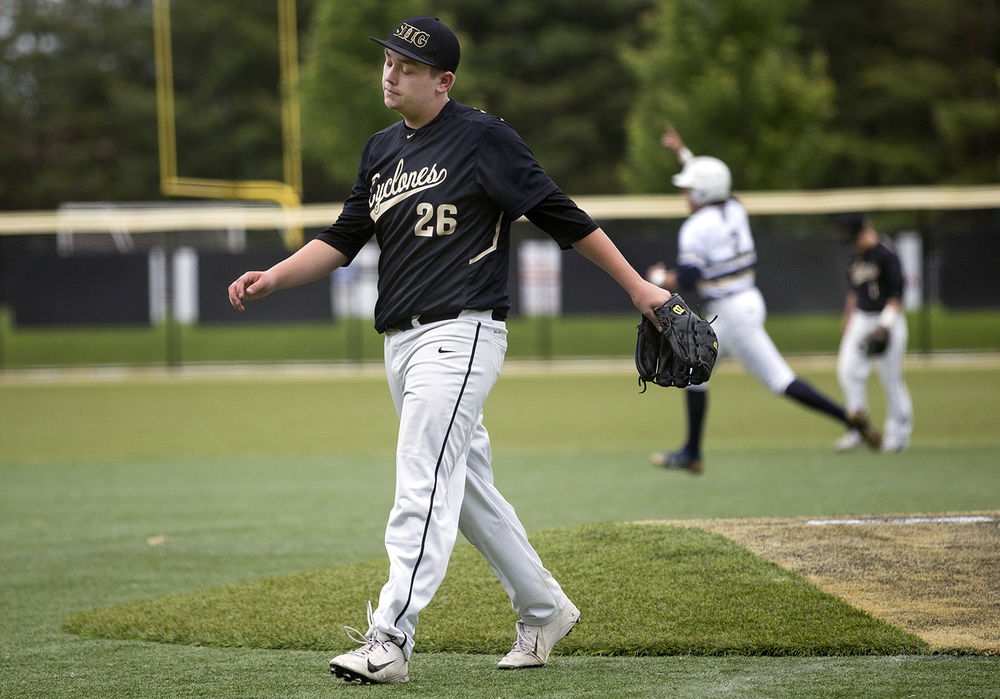 Sacred Heart-Griffin pitcher Austin Chapman walks off the field as Quincy Notre Dame celebrates their 3-2 Class 3A SHG Regional final win Monday, June 1, 2015. With the bases loaded in the seventh inning, Chapman walked the final batter. Ted Schurter/The State Journal-Register