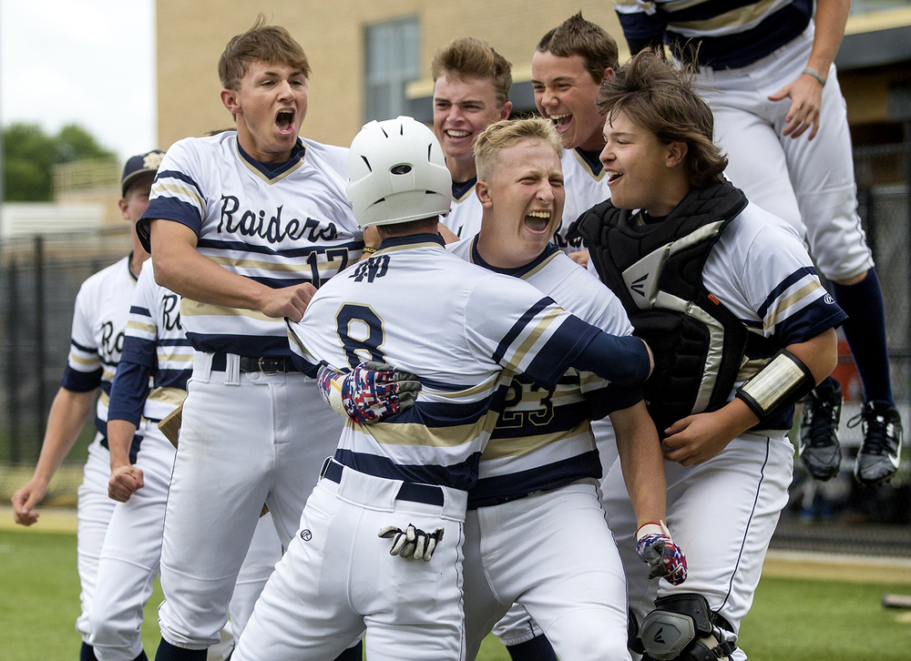 Quincy Notre Dame's Adam Hutson is mobbed by his teammates after scoring on a bases loaded walk against Sacred Heart-Griffin during the Class 3A SHG Regional final Monday, June 1, 2015. Ted Schurter/The State Journal-Register