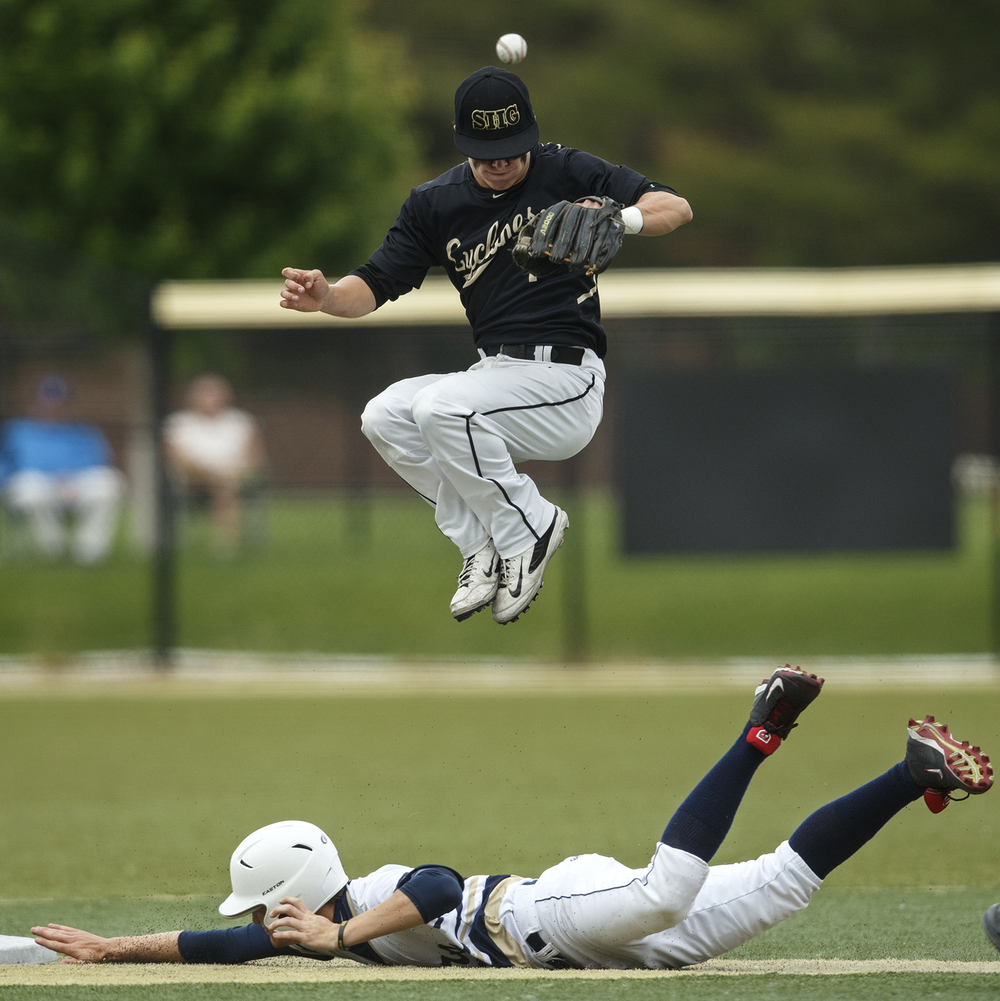 Sacred Heart-Griffin's Clayton Taylor misses the ball as he leaps above Quincy Notre Dame's sliding Johny Ray during the Class 3A SHG Regional final Monday, June 1, 2015. Ted Schurter/The State Journal-Register