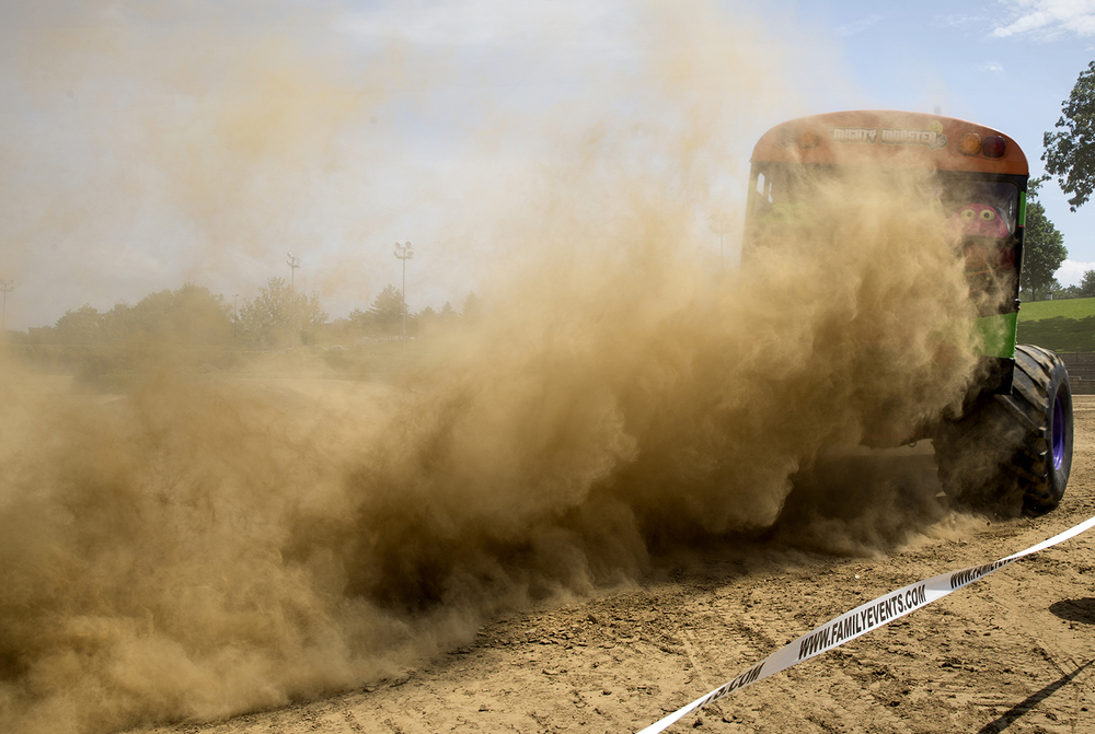 """Mighty Monster,"" a monster truck passenger bus that provides paid rides, kicks up a rooster tail of dust as it roars around the dirt track at the Lucas Oil Monster Truck Nationals at the Multi-Purpose Arena at the Illinois State Fairgrounds Sunday, June 6, 2015.  Ted Schurter/The State Journal-Register"