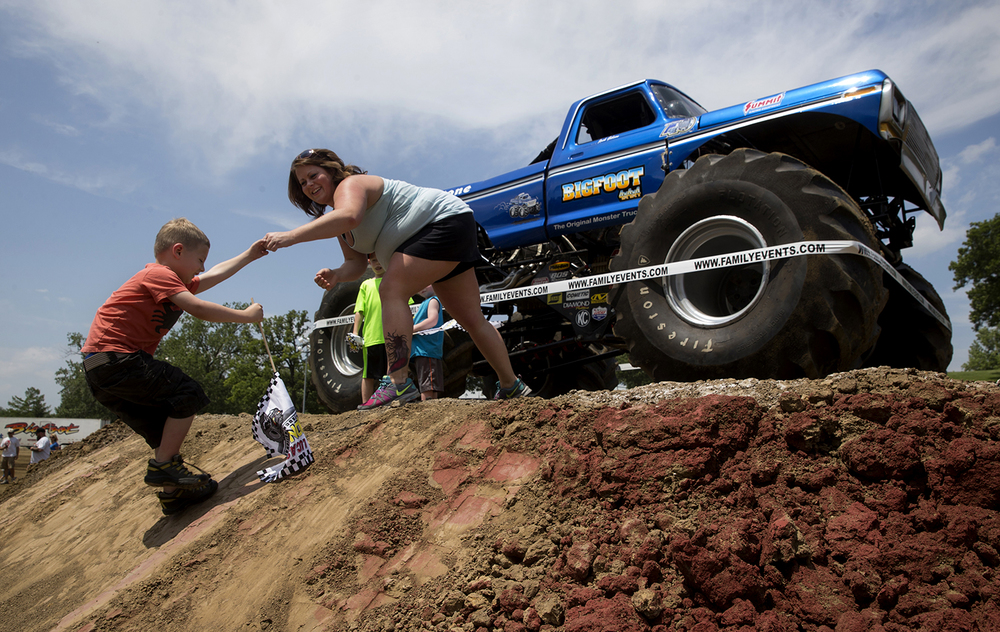 Melissa Garcia helps her son five-year-old son Corben up a steep hill to get closer to the monster truck Bigfoot at the Lucas Oil Monster Truck Nationals at the Multi-Purpose Arena at the Illinois State Fairgrounds Sunday, June 6, 2015.  Ted Schurter/The State Journal-Register