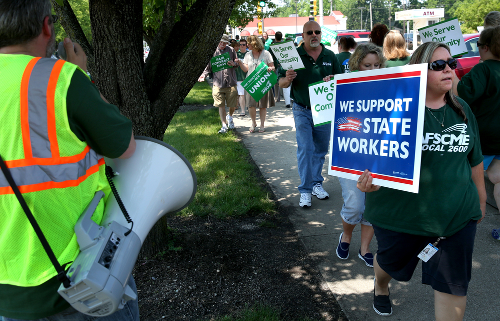 State of Illinois employees walk and chant slogans with the accompanyment of an organizer at left using a loudspeaker along the sidewalk in front of the Prescott Bloom Building where the Illinois Department of Healthcare and Family Services is based. David Spencer/The State Journal-Register