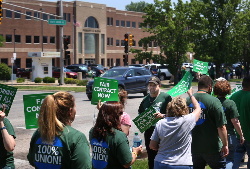 State of Illinois employees walk and chant slogans in front of the Department of Human Services building on South Grand Ave. Tuesday afternoon with other marchers on sidewalk in front of the Department of Healthcare and Family Services in background. David Spencer/The State Journal-Register