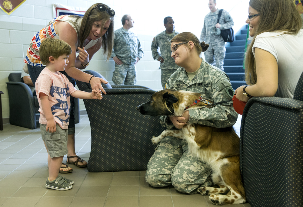 April Hawes holds her son Elijah's hand as he approaches Illinois Army National Guard soldier Aleah Castrejon and her dog Zaine before a deployment ceremony for the 139th Mobile Public Affairs Detachment at Camp Lincoln Sunday, June 7, 2015. Castrejon brought Zaine with her so she could take him to a nearby park one and play one last time before deploying to Cuba.  Ted Schurter/The State Journal-Register