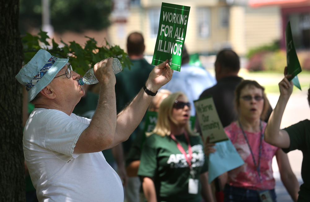 State retiree Ken Rhinehart of Springfield took part in the Tuesday rally and was cooling off with a swig of water in the shade in front of the Jesse B. Harris Building where the Department of Human Services is based. In advance of a June 30th contract deadline, over 100 AFSCME state of Illinois union members held a rally and marched together in front of the Departments of Healthcare and Family Services (HFS) and Human Services (DHS) in Springfield during the lunch hour on Tuesday, June 9, 2015. The union members said they are looking to get a fair contract from Ill Gov. Bruce Rauner. A separate rally with AFSCME members also took place in front of the Illinois Department of Revenue building on Jefferson St. David Spencer/The State Journal-Register