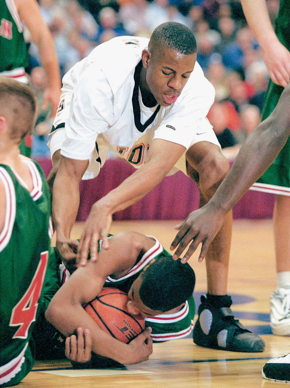 Lincoln's Chris Bunch tries to protect a loose ball from the prying hands of Lanphier's Andre Iguodala during a Sectional game at the Prairie Capital Convention Center March 5, 2002. File/The State Journal-Register
